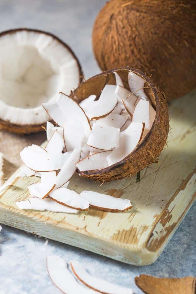 Cut coconut with coconut slithers on a cutting board